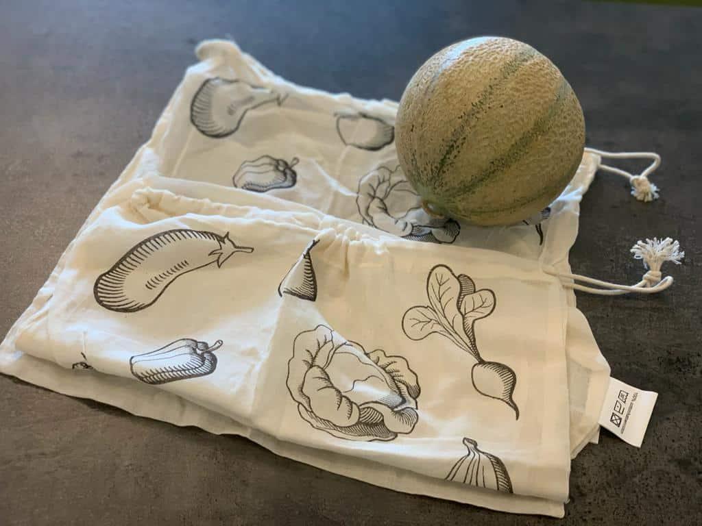 reusable cloth bag next to a melon